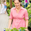Woman at garden centre shopping for flowers — Stok fotoğraf
