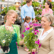 Customer at garden centre buying potted flowers — Stockfoto