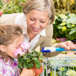 Garden center girl with grandmother smell flower — Stock Photo #12060279