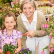 Senior woman and girl in garden center - 图库照片