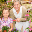 Senior woman and girl in garden center - Stock Photo