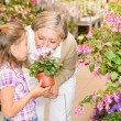 Garden center girl with grandmother smell flower — Stock Photo