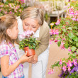 Garden center girl with grandmother smell flower — Stock Photo #12060292