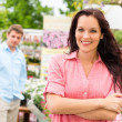 Smiling woman standing at garden center — Stock Photo