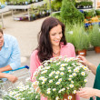 Florist assist woman choose flowers garden store — Stock fotografie