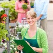 Smiling florist woman at garden centre inventory - Stok fotoğraf