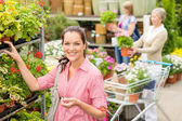 Woman buying potted flower in garden shop — Stock Photo