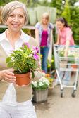 Senior frau halten getopfte blumengarten shop — Stockfoto