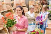 Zahradní centrum žena drží červené hrnkové pelargónie — Stock fotografie