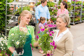 Customer at garden centre buying potted flowers — Stock Photo