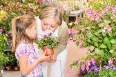 Garden center girl with grandmother smell flower — Stock Photo