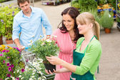 Garden center florist selling flowers to couple — Stock Photo