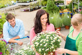 Florist assist woman choose flowers garden store — Stock Photo