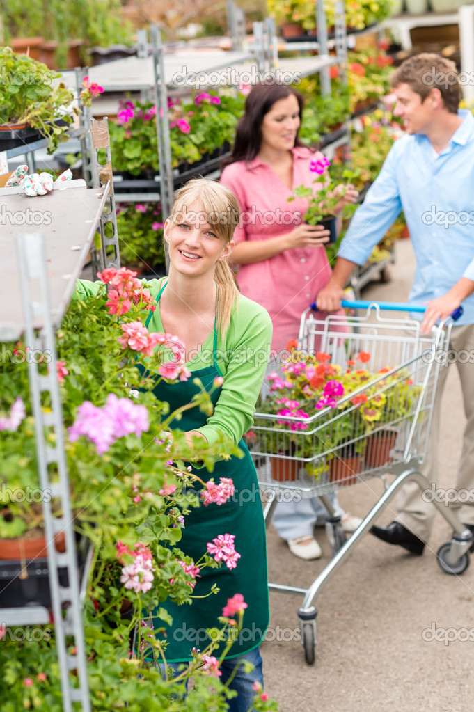 Garden center worker pushing flower shelves customers shopping — Stock fotografie #12060375