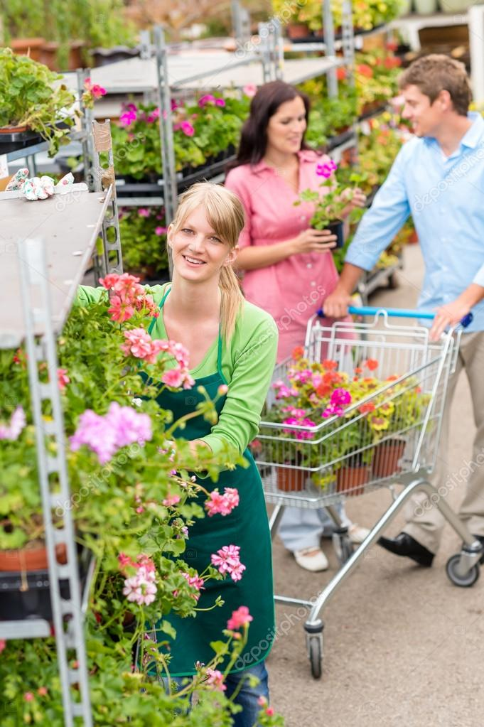 Garden center worker pushing flower shelves customers shopping — Foto Stock #12060375