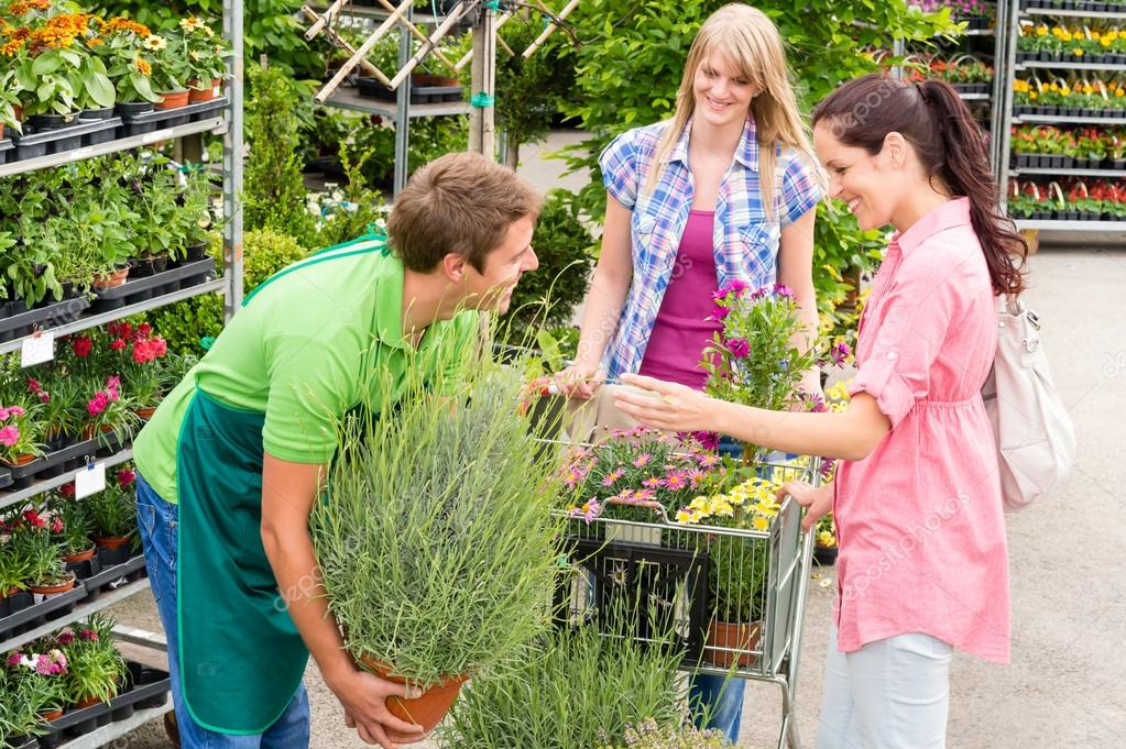 Male garden centre worker selling potted plant to female customers — Stock Photo #12060387