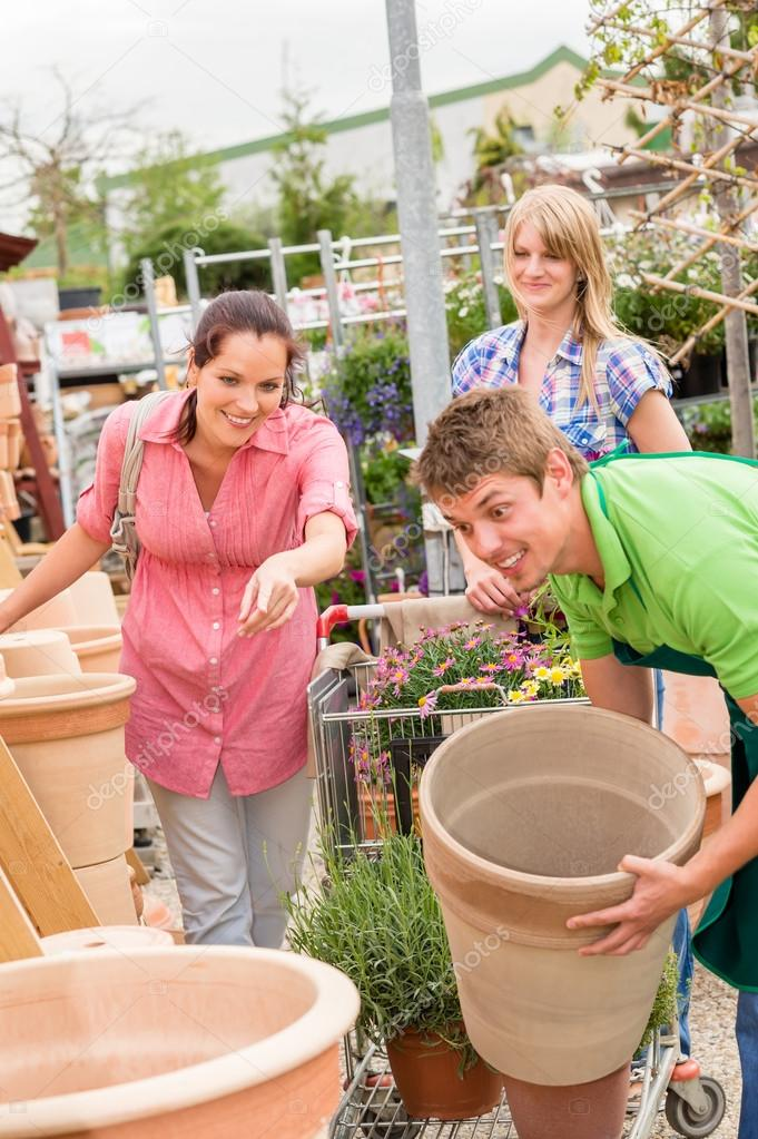 Male worker at garden centre help customer choose flower pot — Stock Photo #12060400