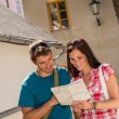 Happy couple looking at map in town - 