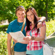 Happy couple looking on map in park — Stock Photo