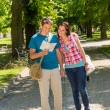 Young couple looking at map in park - Stockfoto