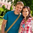 Foto Stock: Young man and woman tourist smiling