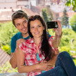 Happy young couple photographing themselves — Stockfoto