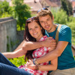 Young happy couple embracing on balcony smiling — Stock Photo
