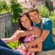 Young happy couple embracing on balcony smiling — Stock Photo #12447415
