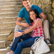 Happy young couple sitting on stairs smiling — Stock Photo
