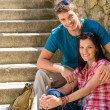 Happy young couple sitting on stairs smiling - Stock Photo