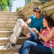 Young couple looking city map sunny day — Stock Photo #12447475