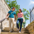Happy couple walk down stairs holding hands — Stock Photo