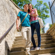 Young happy couple walking down stairs smiling — Stock Photo #12447492