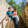 Young happy couple standing on stairs smiling — 图库照片