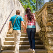 Couple climbing up city stairs holding hands — Foto Stock