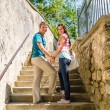 Royalty-Free Stock Photo: Young couple smiling holding hands on stairs