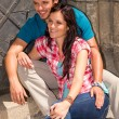 Young couple sitting on building steps smiling — Stockfoto