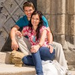 Foto Stock: Young couple sitting on building steps smiling