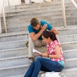 Young couple reading book guide on stairs — Foto Stock #12447542