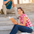 Woman sitting on stairs reading man photographing - Stockfoto