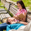 Young happy couple relax on bench park — Stock Photo #12447561