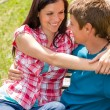 Young happy couple hugging in park sitting — Stock Photo #12447573