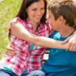 Stock Photo: Young happy couple hugging in park sitting
