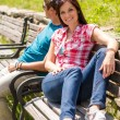 Young couple sitting on bench in park — Stock Photo #12447578