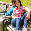 Young couple sitting on bench in park — Stok fotoğraf #12447578