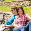 Young couple relaxing on bench in park — Stockfoto