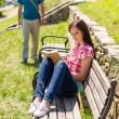 Stock Photo: Woman reading book on bench man coming