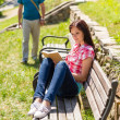 Woman reading book on bench man coming - Stock Photo