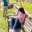 Woman waving to man sitting on bench - Stock Photo