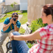 Man taking picture of woman on bench — Stock Photo